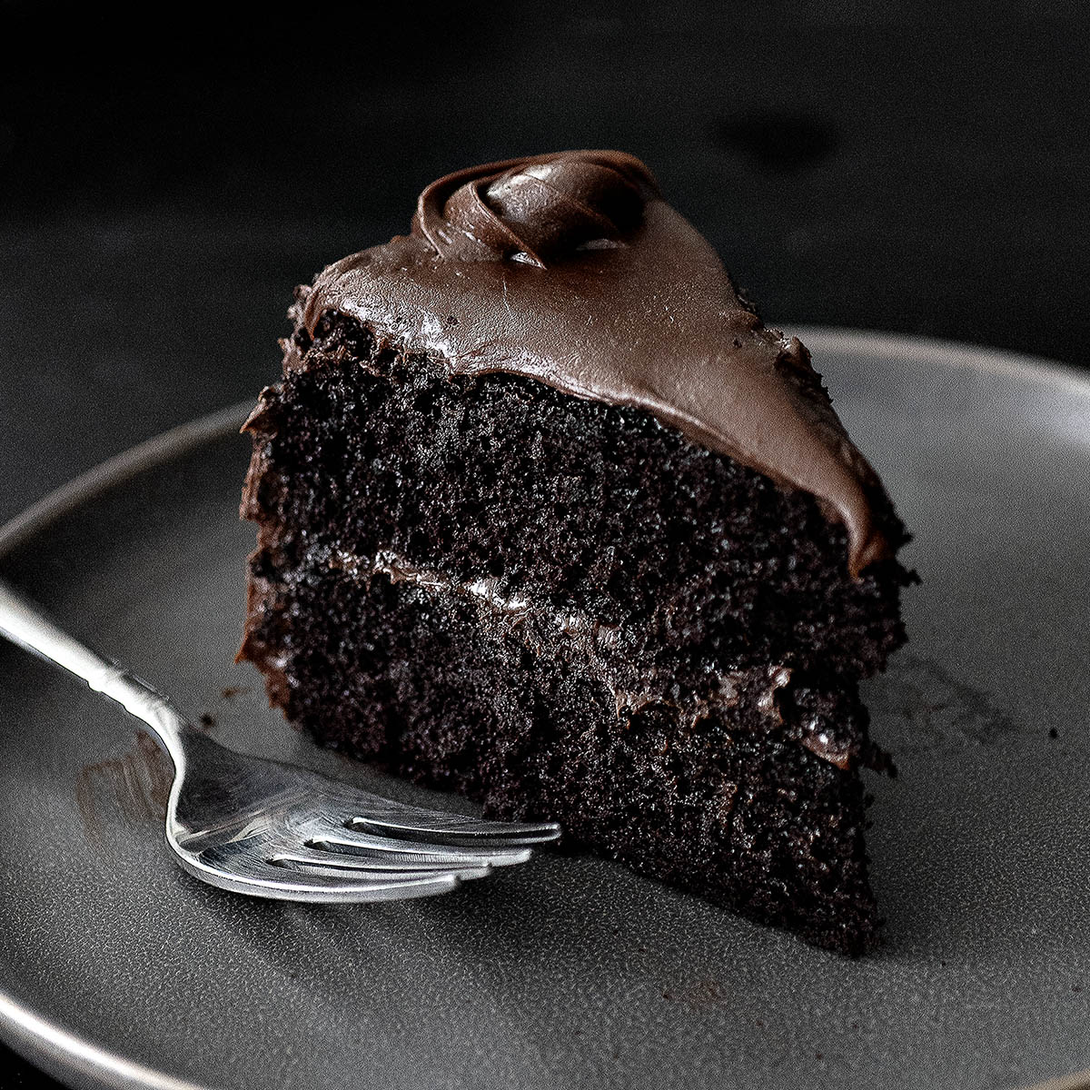 A slice of chocolate layer cake on a dark gray plate with a fork