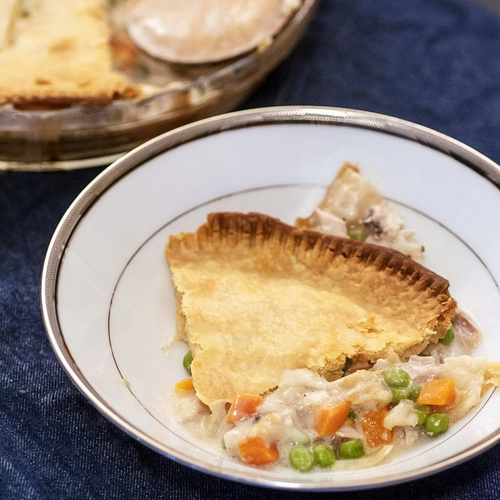 A shallow bowl with a wedge of chicken pot pie on a dark blue background