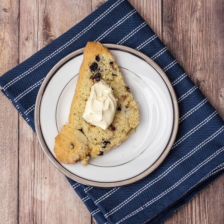 A blueberry scone topped with clotted cream on a white plate