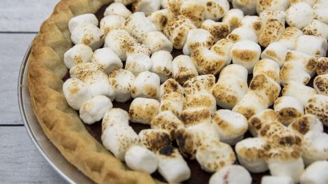 A pie plate of s'mores pie topped with toasted marshmallows