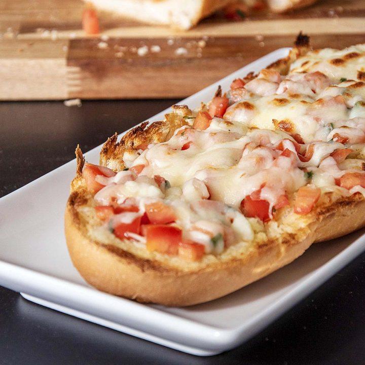 Sliced cheesy bruschetta garlic bread on a white serving tray