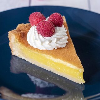 A slice of shortbread lemon tart garnished with whipped cream and raspberries