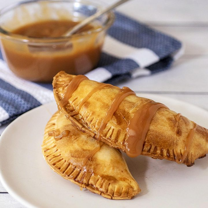 Two air fried empanadas on a plate in front of a dish of caramel sauce.