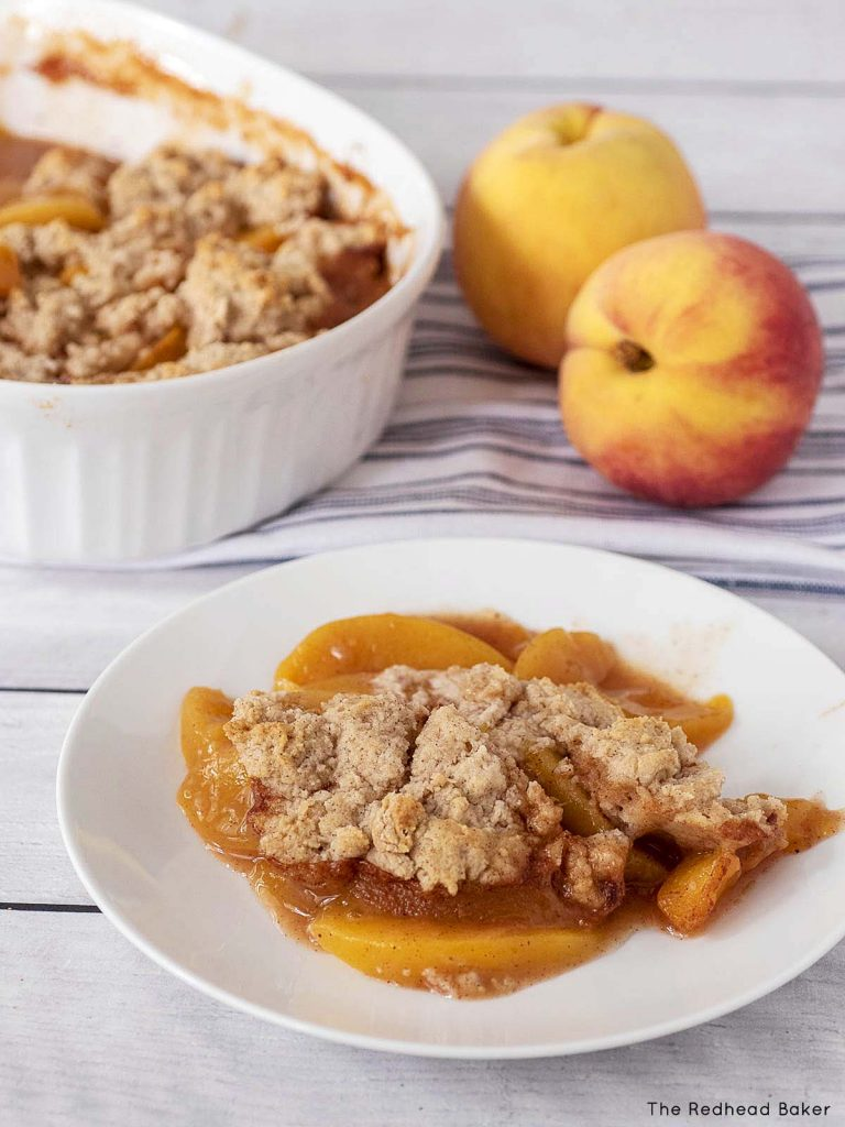 A plate of peach cobbler in front of two fresh peaches and a baking dish