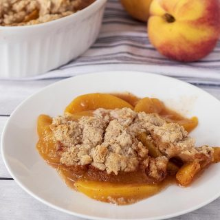 A plate of peach cobbler with cinnamon biscuit topping.
