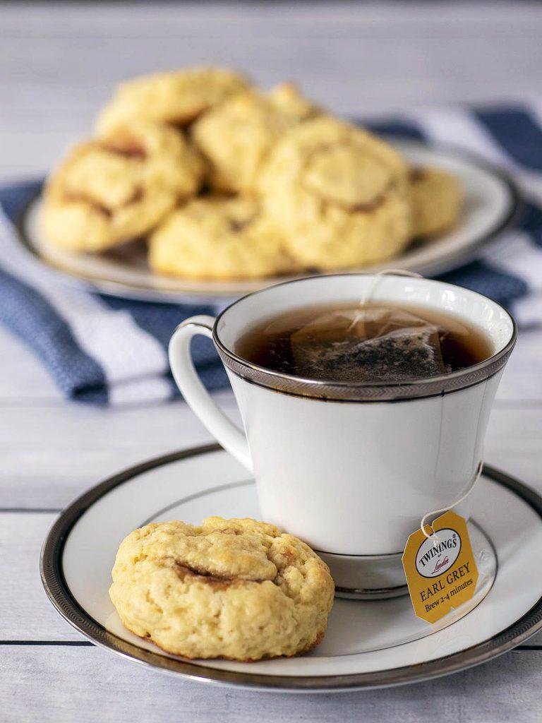 A cup of tea and a tea bun on a saucer