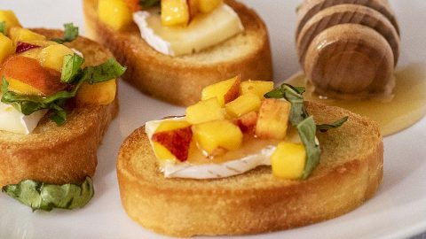 Three pieces of peach bruschetta on a white plate with a honey dipper.