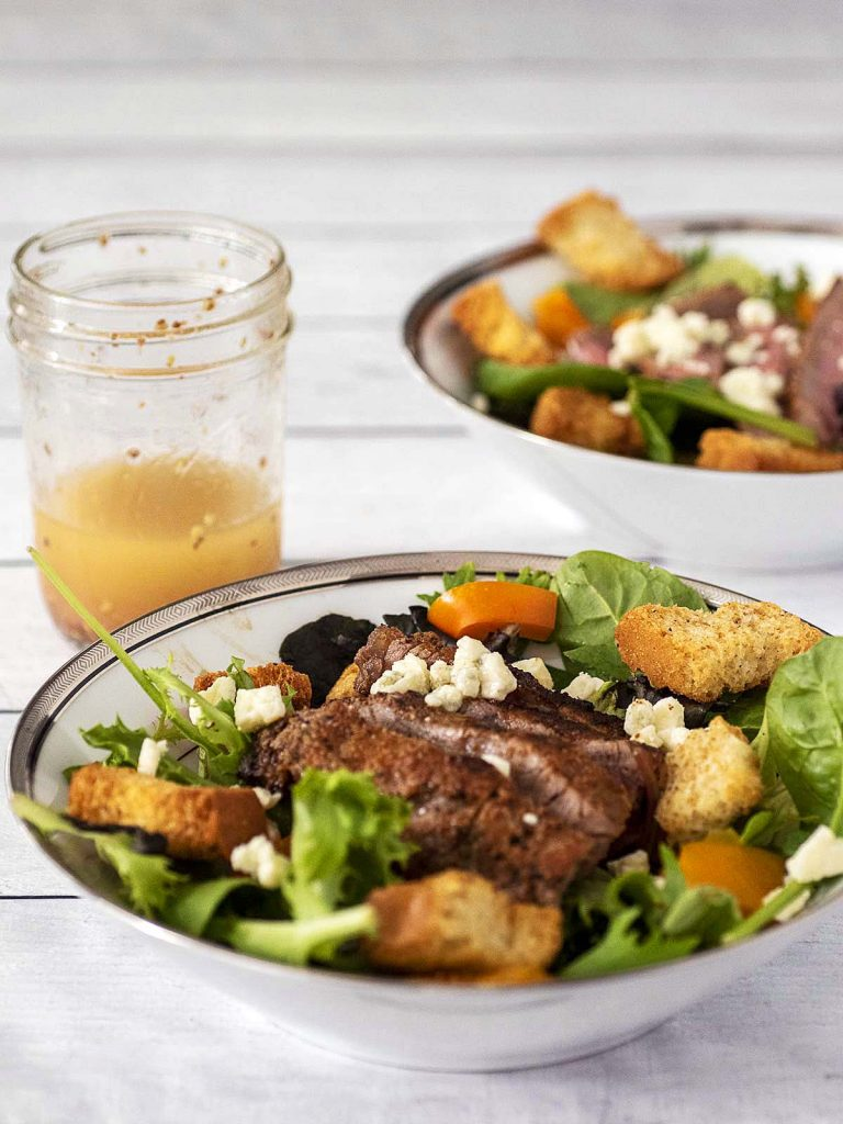 Two bowls of steak and bell pepper salad with a jar of red wine vinaigrette.