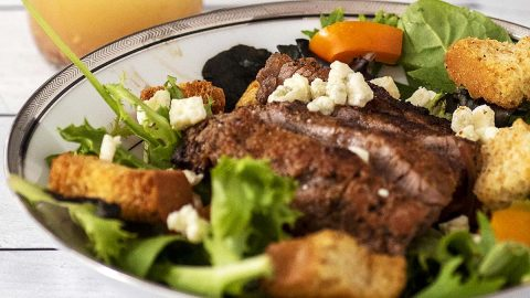 A bowl of steak and bell pepper salad in front of a jar of red wine vinaigrette.