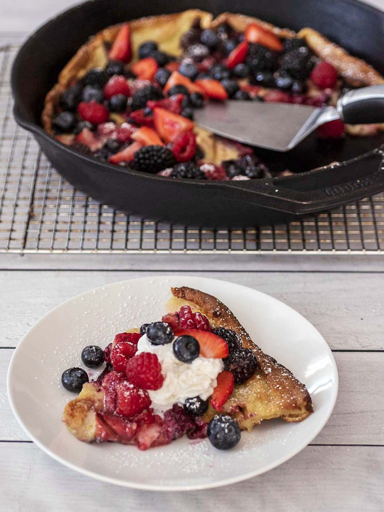 A slice of Dutch baby on a white plate in front of a cast-iron skillet.