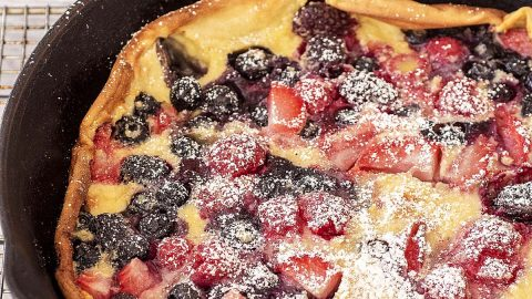 A dutch baby with berries in a cast-iron skillet.
