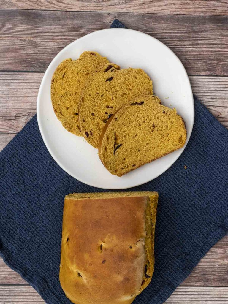 An overhead view of three slices of pumpkin cranberry yeast bread on a white plate.