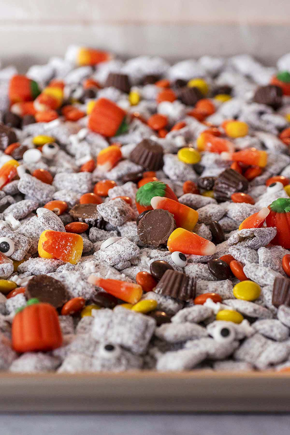 Halloween muddy buddies spread out on a cookie sheet.