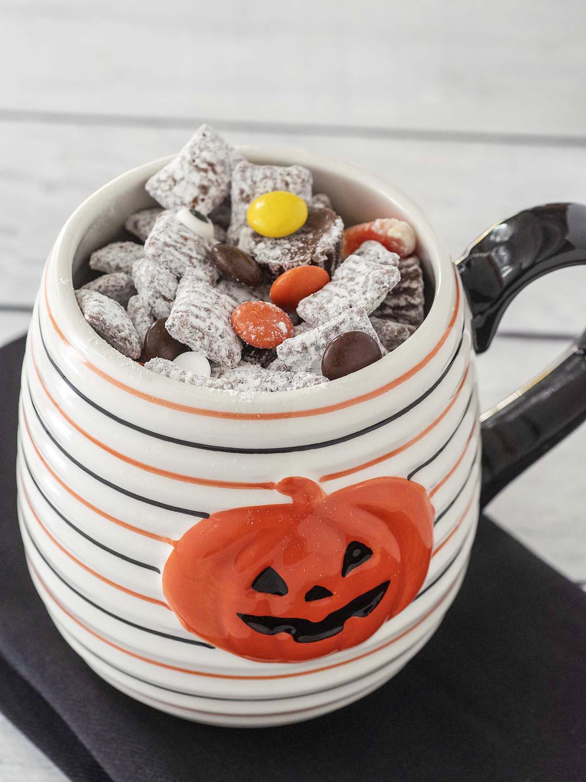 A white-with-black-and-orange striped jack-o-lantern mug full of Halloween Muddy Buddies.