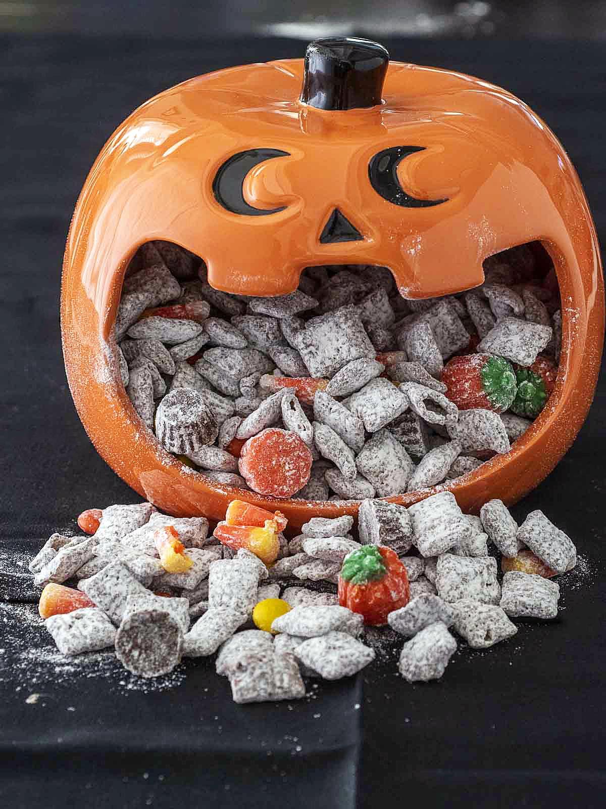A jack-o-lantern candy dish full of Halloween Muddy Buddies.