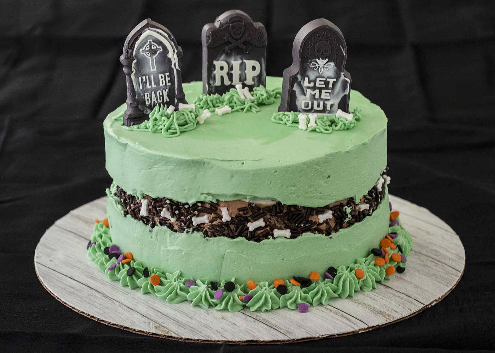 A fully decorated graveyard fault line cake on a black tablecloth.