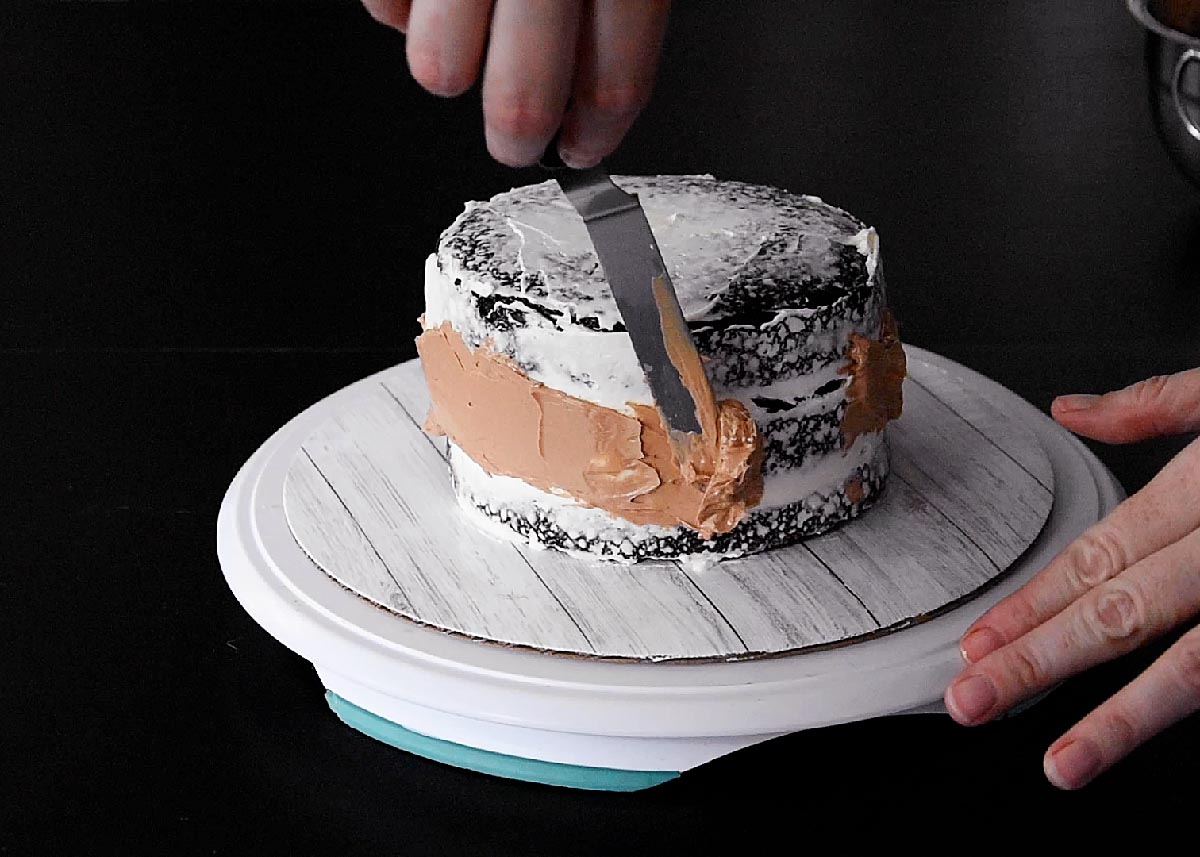 Spreading a ribbon of chocolate frosting onto the cake.