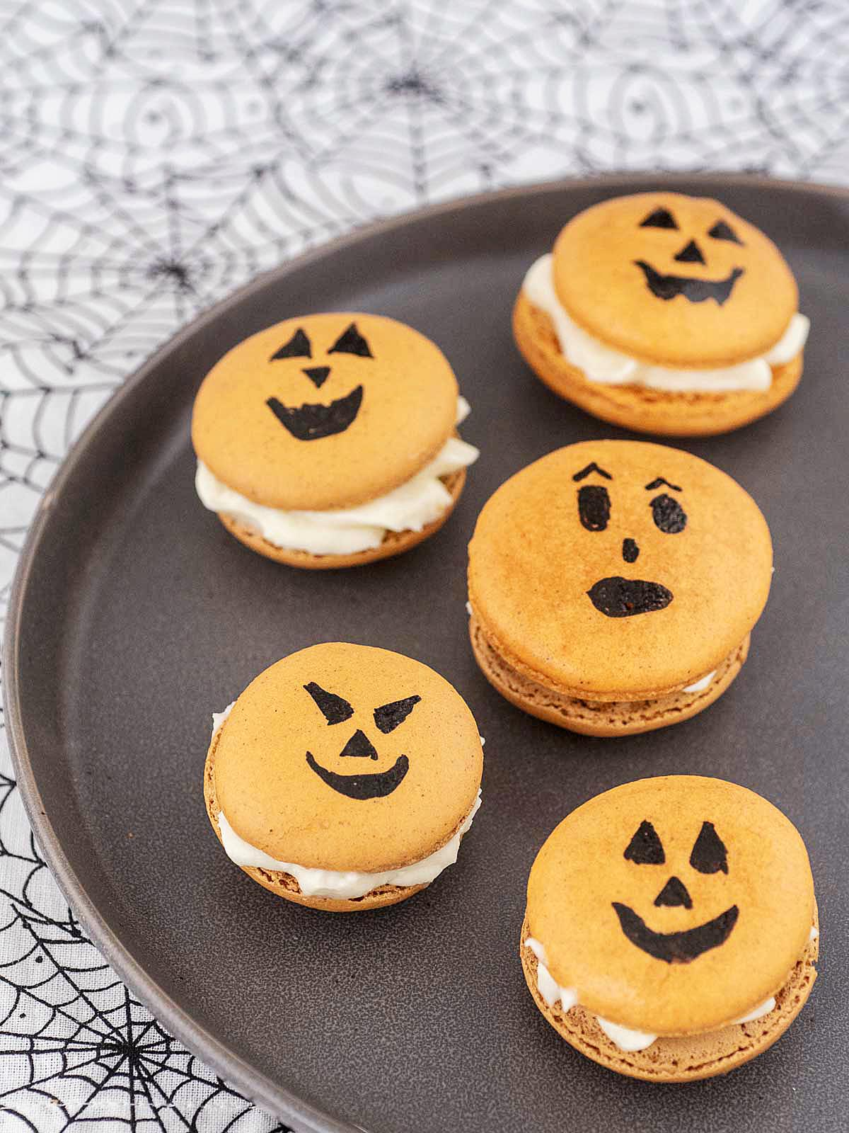 Five jack-o-lantern macarons on a black plate on a spiderweb tablecloth.