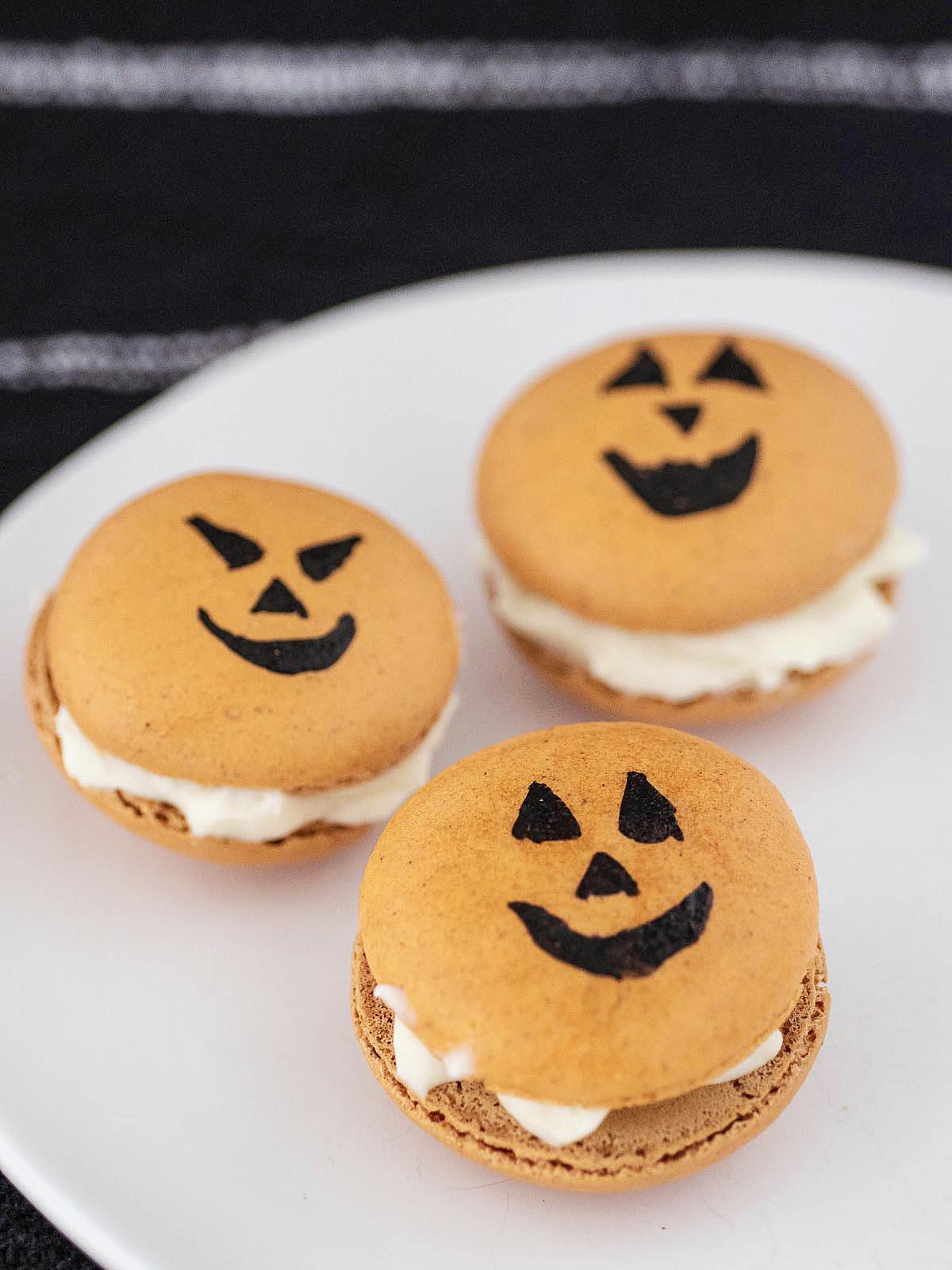 Three Halloween macarons on a white plate.