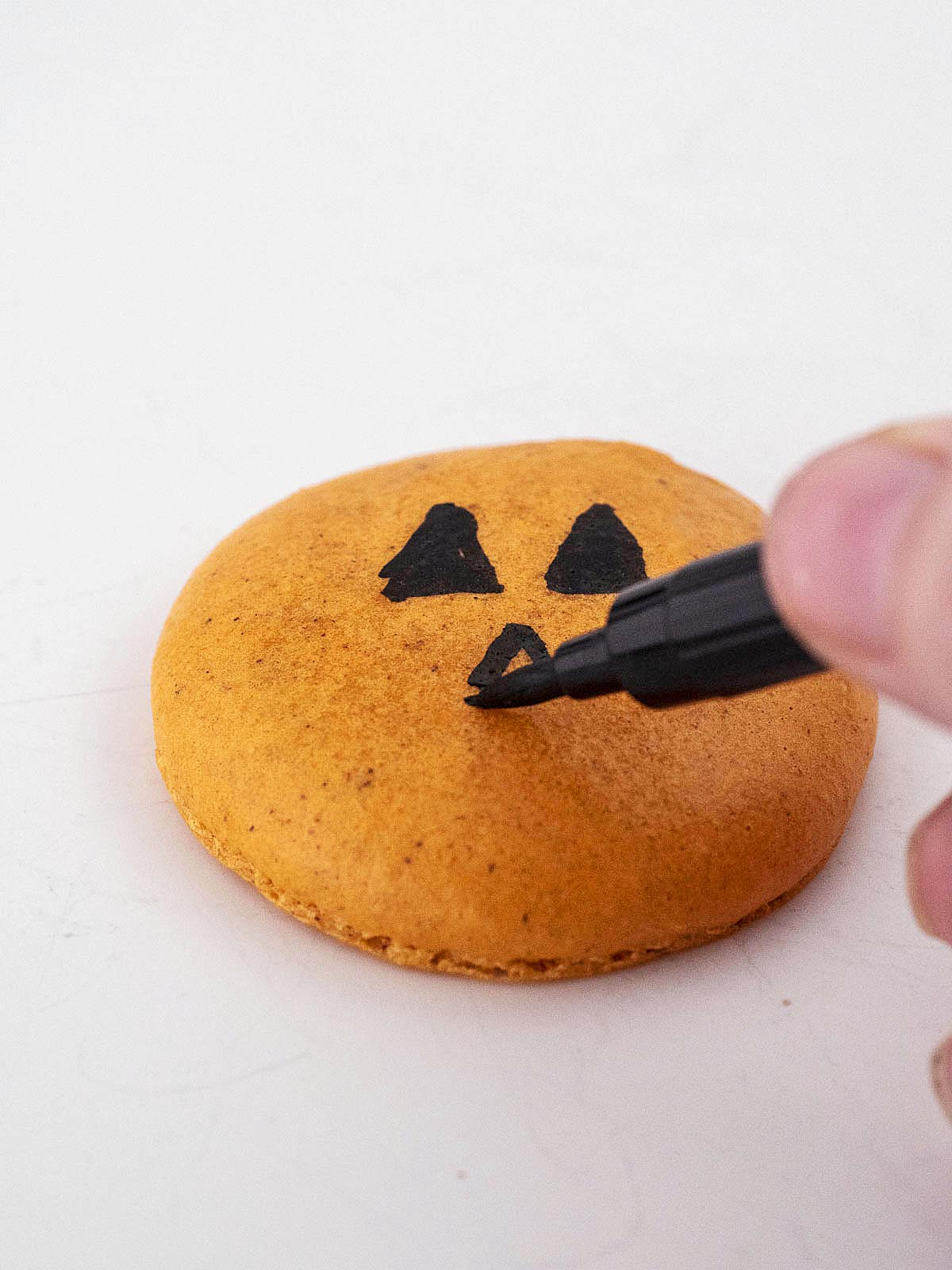 Drawing a face on a macaron shell with a food coloring pen.