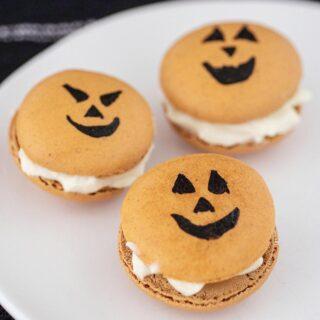 Three Halloween macarons on a white plate