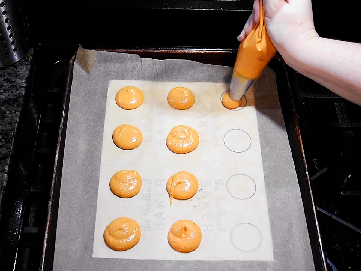 PIping macaron batter onto a parchment-paper-lined cookie sheet with a template underneath.