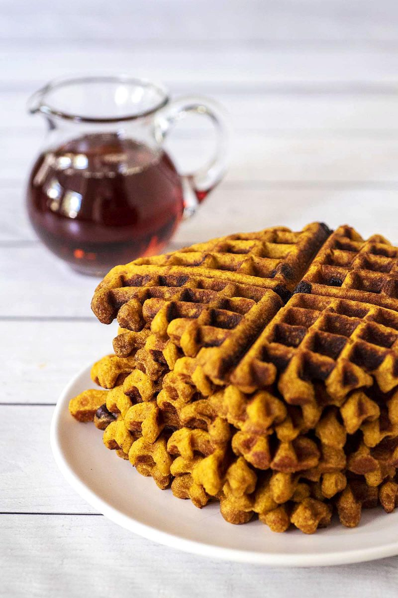 A stack of pumpkin chocolate chip waffles on a white plate.