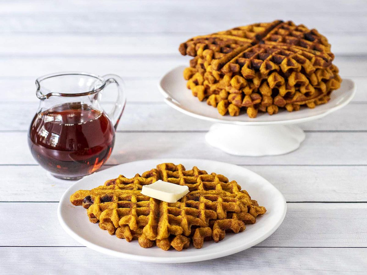 A syrup jar, a white plate with two waffles, and a stack of waffles in the background.
