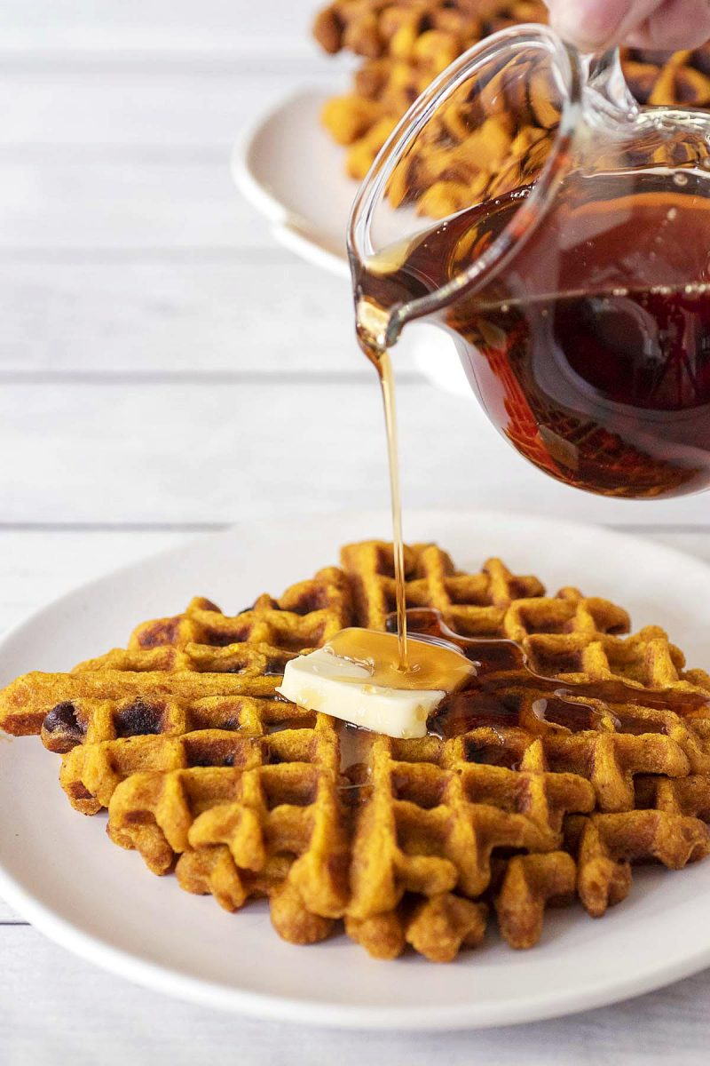 Syrup being poured onto two pumpkin chocolate chip waffles.