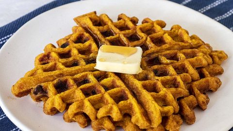 Two pumpkin chocolate chip waffles on a white plate with butter and syrup.